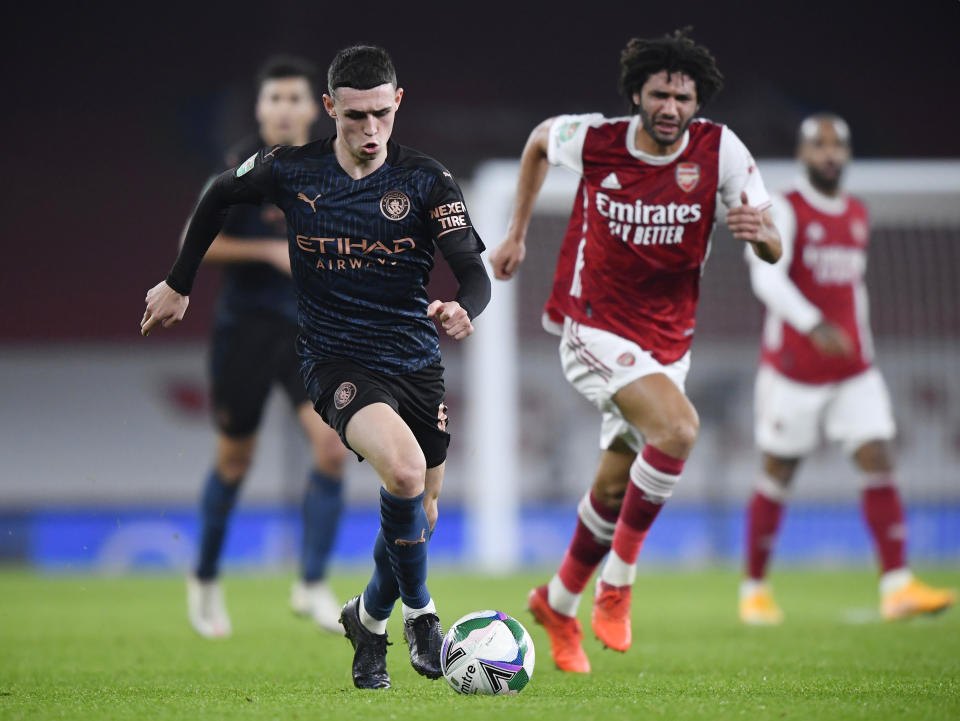 Manchester City's Phil Foden (left) battles with Arsenal's Mohamed Elneny.