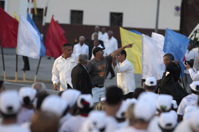 "A man is taken away by security as he shouts ""down with the revolution, down with the dictatorship"" shortly after Pope Benedict XVI arrived at Revolution Square to conduct a Mass in Santiago de Cuba, Cuba, Monday, March 26, 2012. Pope Benedict XVI is in Cuba for a three-day visit. (AP Photo/Esteban Felix)"