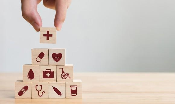 Hand stacking wood blocks with healthcare-related icons printed on them