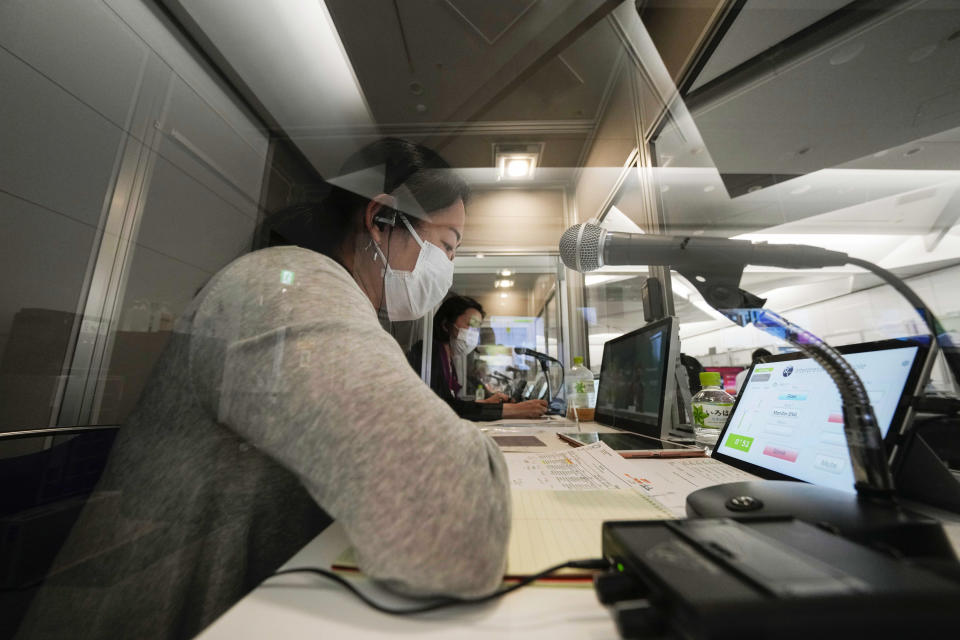 Interpreters work at the main press center at the 2020 Summer Olympics, Friday, July 30, 2021, in Tokyo, Japan. Unlike previous Olympics, all the interpretation is being done remotely with most interpreters working in booths at the main center. About two dozens interpreters aren't even in the country, chiming in from the Americas or Europe to handle late night events in Japan. (AP Photo/Luca Bruno)