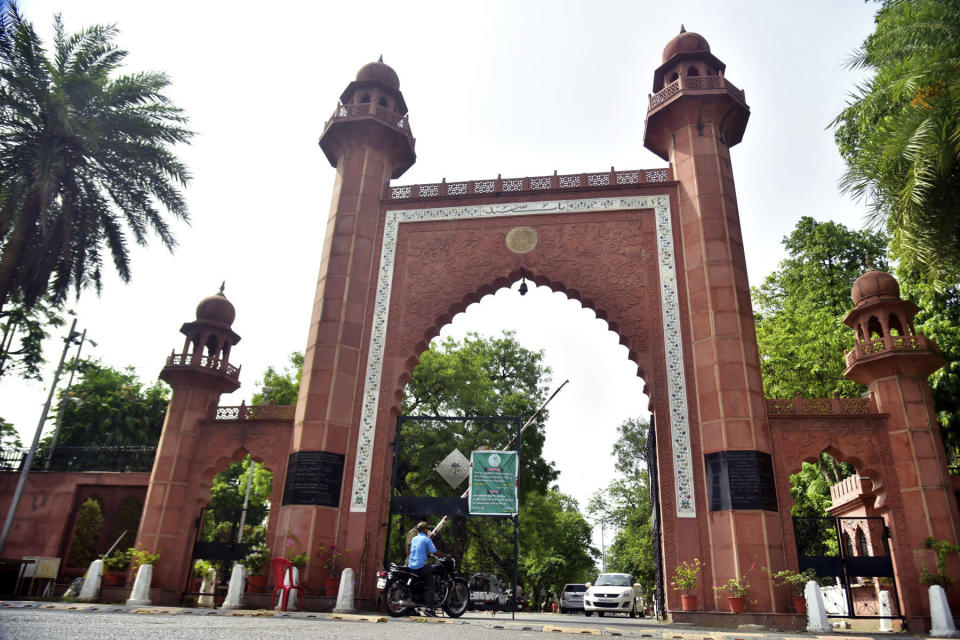 A motorcyclist enters the gate of Aligarh Muslim University in Aligarh, India, Saturday, June 12, 2021. Within just one month, the official Facebook page of Aligarh Muslim University, one of the topmost in India, published about two dozen obituaries of its teachers, all lost to the pandemic. Across the country, the deaths of educators during the devastating surge in April and May have left students and staff members grief-stricken and close-knit university communities shaken. (AP Photo/Manoj Aligadi)