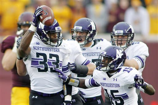 Northwestern linebacker David Nwabuisi (33) celebrates with teammate Daniel Jones (15) after intercepting a pass in the first half of an NCAA college football game against Minnesota in Minneapolis Saturday, Oct. 13, 2012.(AP Photo/Andy King)