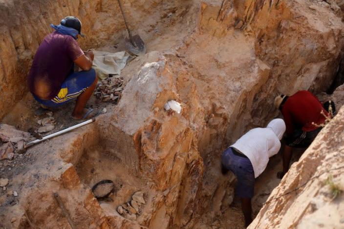Indigenous people work in a gold mine at the Napoleao community in the Raposa Serra do Sol reservation