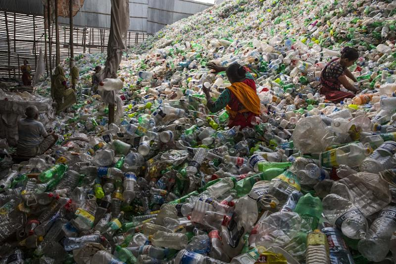 Women sorting discarded plastic bottles to be recycled in Dhaka, Bangladesh, in a photograph at the ArtScience Museum's Planet Or Plastic exhibition by National Geographic. (Photo: Randy Olson)