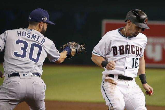 Arizona Diamondbacks' Tim Locastro (16) gets safely back to first base as San Diego Padres first baseman Eric Hosmer (30) applies a late tag on a pickoff-attempt during the first inning of a baseball game Friday, Sept. 27, 2019, in Phoenix. (AP Photo/Ross D. Franklin)