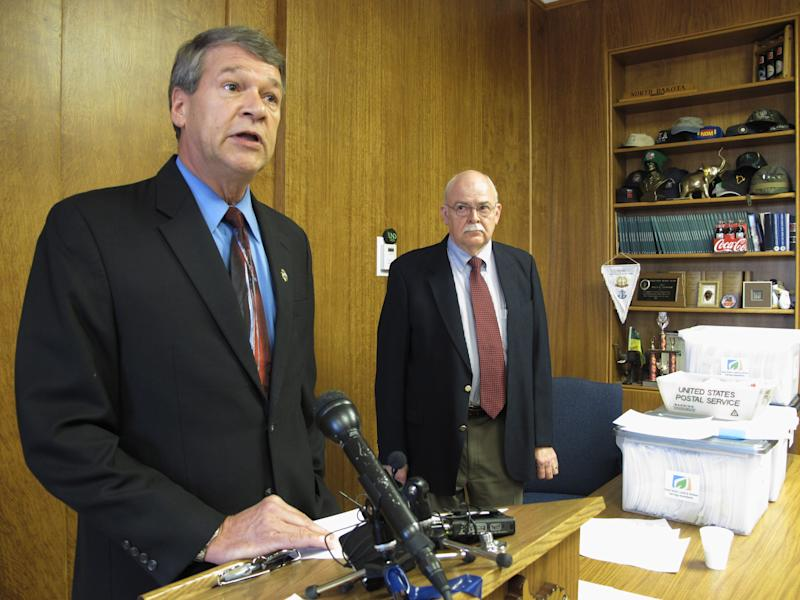 North Dakota Attorney General Wayne Stenehjem, left, speaks while North Dakota Secretary of State Al Jaeger listens at a news conference on the results of an investigation into petition fraud, Tuesday, Sept. 4, 2012 in Stenehjem's office at the Capitol in Bismarck, N.D., Two proposed ballot measures _ to create a North Dakota conservation fund and make marijuana use legal for medical treatments _ were disqualified from the ballot because hundreds of the initiative petition signatures were allegedly forged or made up. Eight North Dakota State University football players are among the 11 petition circulators who are facing charges. (AP Photo/Dale Wetzel)