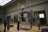 Workers at the Louvre museum set up a scaffolding in Paris, Tuesday, Feb. 9, 2021. The forced closure has granted museum officials a golden opportunity to carry out long-overdue refurbishments that were simply not possible with nearly 10 million visitors a year. (AP Photo/Thibault Camus)