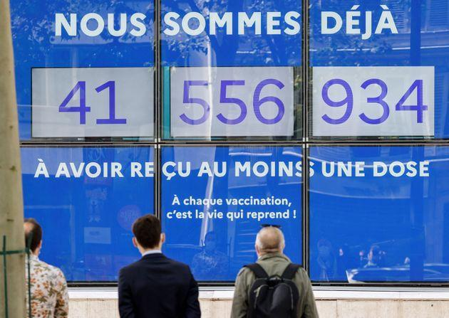 People look at screens showing live the number of French people who received at least a first dose of a vaccine against the Covid-19 on a facade of the Solidarity and Health Ministry in Paris, on July 30, 2021. - 50% of the French population is now fully vaccinated. (Photo by Ludovic MARIN / AFP) (Photo by LUDOVIC MARIN/AFP via Getty Images) (Photo: LUDOVIC MARIN via Getty Images)