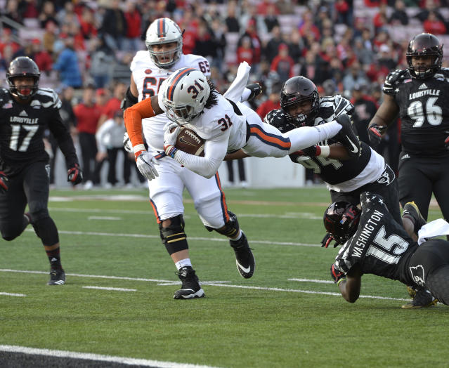 "Virginia running back <a class=""link rapid-noclick-resp"" href=""/ncaaf/players/256995/"" data-ylk=""slk:Chris Sharp"">Chris Sharp</a> (31) dives for the end zone over the defense of Louisville defensive tackle G.G. Robinson (94) and cornerback <a class=""link rapid-noclick-resp"" href=""/ncaaf/players/240732/"" data-ylk=""slk:Trumaine Washington"">Trumaine Washington</a> (15) during the first half of an NCAA college football game, Saturday, Nov. 11, 2017, in Louisville, Ky. (AP Photo/Timothy D. Easley)"