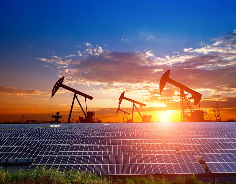 Oil pumps under the setting sun with solar panels in the foreground.