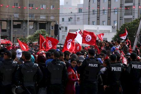 Tunisians wave their national flags during a march against extremism outside the Bardo Museum in Tunis