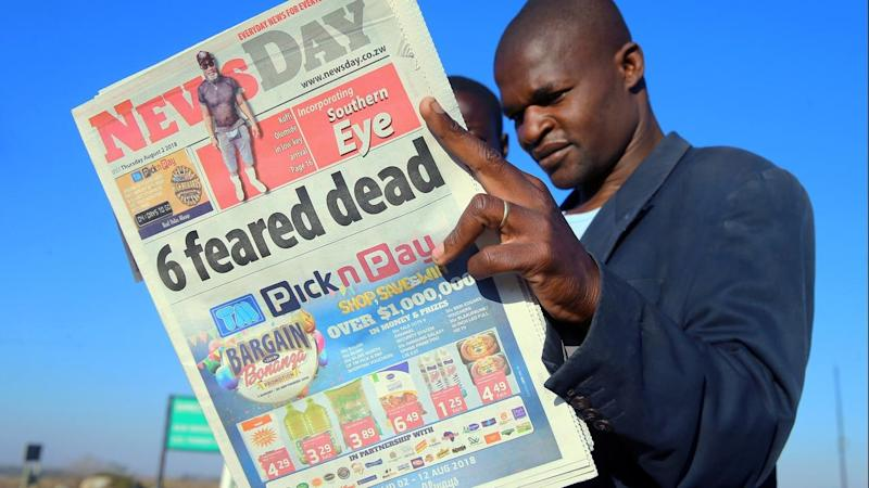 A man in Zimbabwe reads a newspaper following post-election violence in the capital Harare