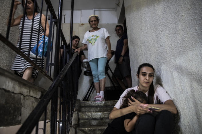 People in Ashdod, Israel take shelter in the stairwell of their apartment building during a siren warning of rockets fired from Gaza to Israel on May 18, 2021.(AP Photo/Heidi Levine)