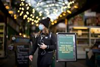 Signs tell visitors to Borough Market in London that masks are now mandatory