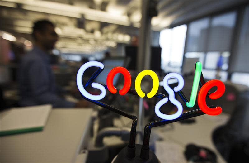 A neon Google logo is seen as employees work at the new Google office in Toronto