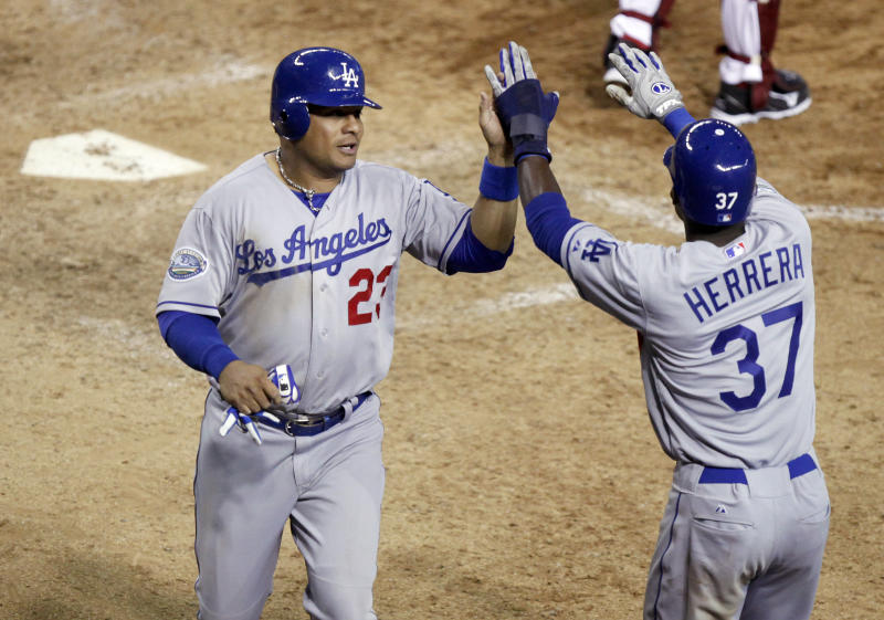 Los Angeles Dodgers' Bobby Abreu, left, is congratulated by teammate Elian Herrera, right, after Abreu scored the go-ahead run against the Arizona Diamondbacks in the ninth inning of a baseball game Tuesday, May 22, 2012, in Phoenix.(AP Photo/Paul Connors)
