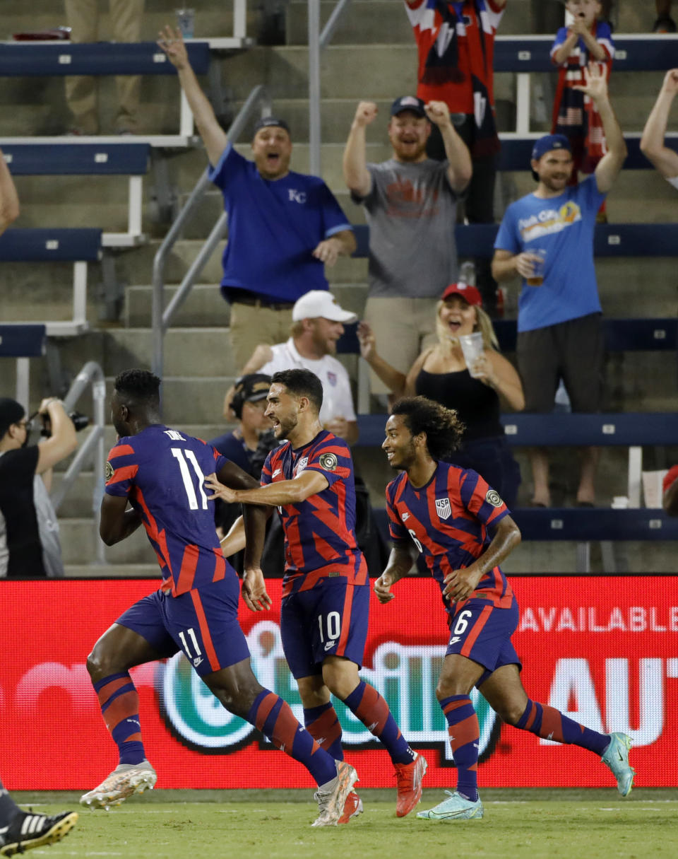 U.S. forward Daryl Dike (11) celebrates with Cristian Roldan (10) and Gianluca Busio (6) after scoring a goal in the first half of the team's CONCACAF Gold Cup soccer match against Martinique in Kansas City, Kan., Thursday, July 15, 2021. (AP Photo/Colin E. Braley)