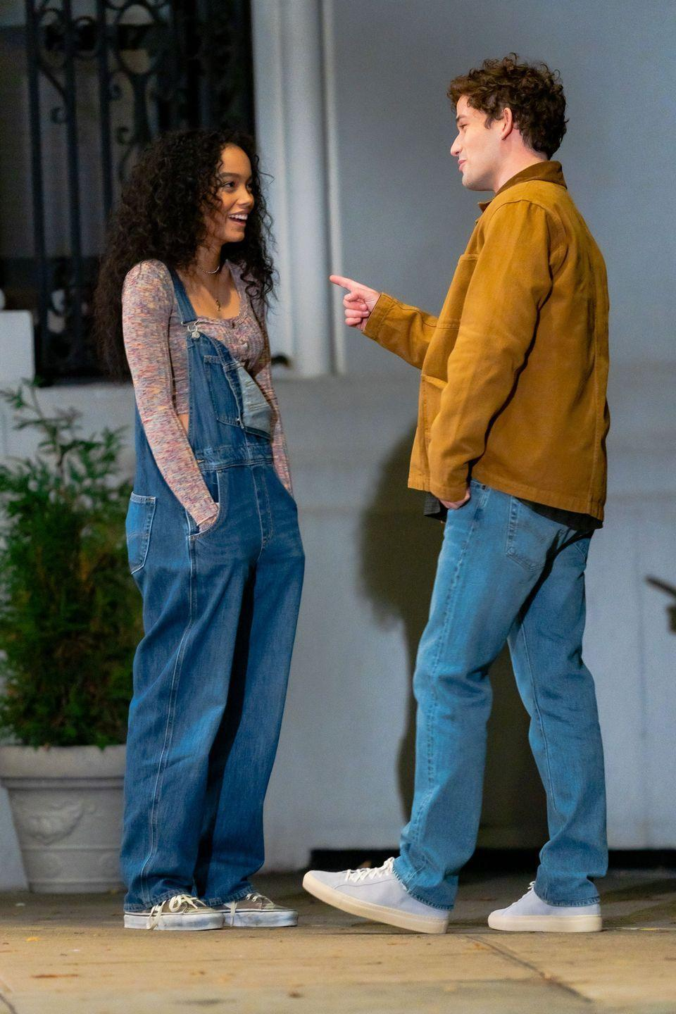 <p>Whitney Peak, in baggy overalls, a cropped sweater, and sneakers, chats with Eli Brown. </p>