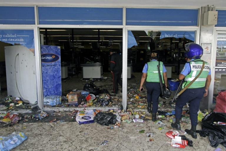 Police officers enter a supermarket after lootings during anti-government protests