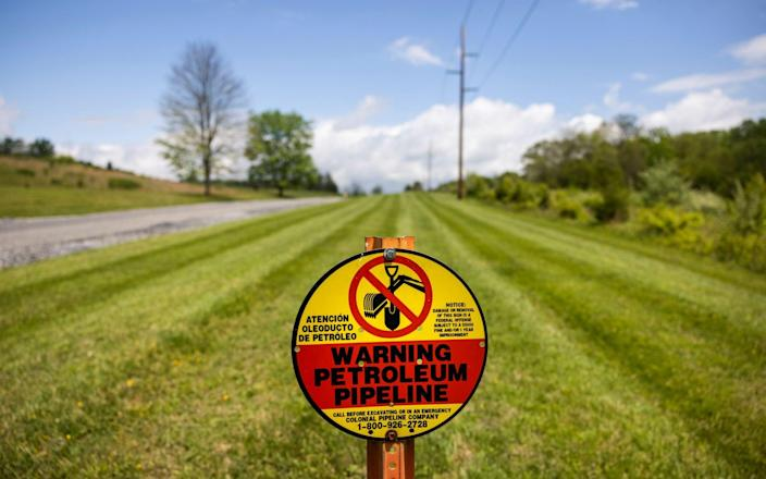 A sign marks the below-ground location of a Colonial Pipeline petroleum pipeline in Woodbine, Maryland, USA - Jim Lo Scalzo/Shutterstock
