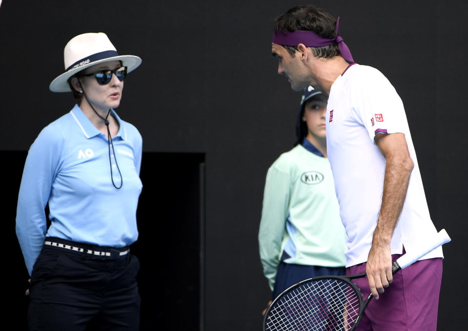 FILE - In this Jan. 28, 2020 file photo, Switzerland's Roger Federer, right, questions a line judge during his quarterfinal against Tennys Sandgren of the U.S. at the Australian Open tennis championship in Melbourne, Australia. In a Grand Slam-first, at the 2021 Australian Open tennis championships, there will be no on-court line judges on any of the tournament courts in an effort to reduce the number of staff on-site due to coronavirus-related concerns. Only chair umpires and ball persons will be on the court. (AP Photo/Andy Brownbill,File)