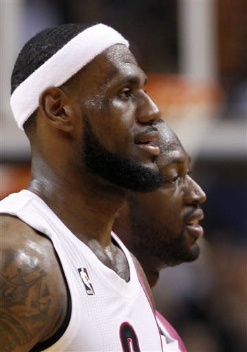 Miami Heat's LeBron James, left, and Dwyane Wade head for a time out in the second half of an NBA basketball game against the Toronto Raptors in Miami, Sunday, Feb. 5, 2012. The Heat won 95-89. (AP Photo/Alan Diaz)