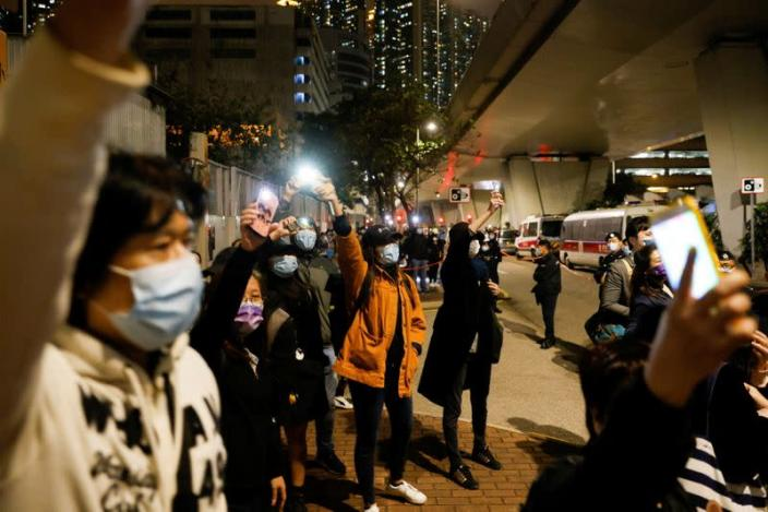 Supporters of pro-democracy activists wave flashlights as a prison van which is carrying some of 47 pro-democracy activists charged with national security law leaves West Kowloon Magistrates' Courts, in Hong Kong