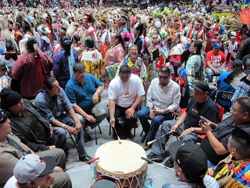 A steady stream of Native American and indigenous dancers file past a drumming group at the 30th annual Gathering of Nations in Albuquerque, N.M., on Friday, April 26, 2013. The powwow draws hundreds of competitive dancers and tens of thousands of spectators each year. (AP Photo/Susan Montoya Bryan)