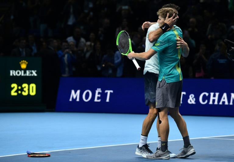 Bulgaria's Grigor Dimitrov (L) hugs Belgium's David Goffin as he celebrates winning the ATP World Tour Finals