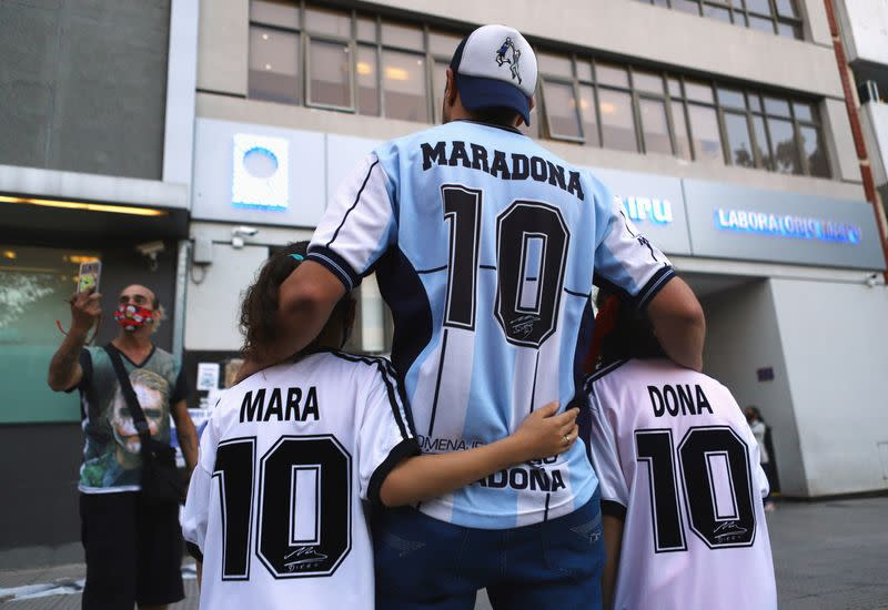 FILE PHOTO: Fans of Argentine soccer great Diego Maradona pose for a photograph outside the clinic where Maradona underwent brain surgery, in Olivos