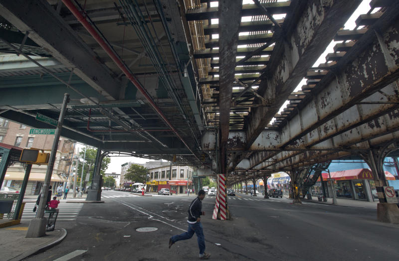 "A young man runs under an elevated section of subway tracks in The Bronx borough of New York,  Wednesday, May 22, 2013.  A company that offered tourist treks to the Bronx ""ghetto"" has shut down under scathing criticism from neighborhood leaders offended by the tours that took mostly European and Australian tourists past food-pantry lines and ""pickpocket"" park. But other New York companies continue to show visitors,  many of them foreigners who know of the Bronx only from movies, the grittiest part of the city's poorest borough. (AP Photo/Richard Drew)"