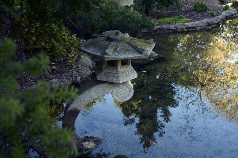 A vintage stone lantern hangs over a reflecting pond with images of autumn trees on its surface in the Japanese Garden at Lotusland, Monday, Nov. 23, 2020, in Montecito, Calif. The recently reconstructed pond has a new liner and biofiltration system for improved water clarity, where koi, several aquatic plants and lotuses are viewed. (AP Photo/Pamela Hassell)