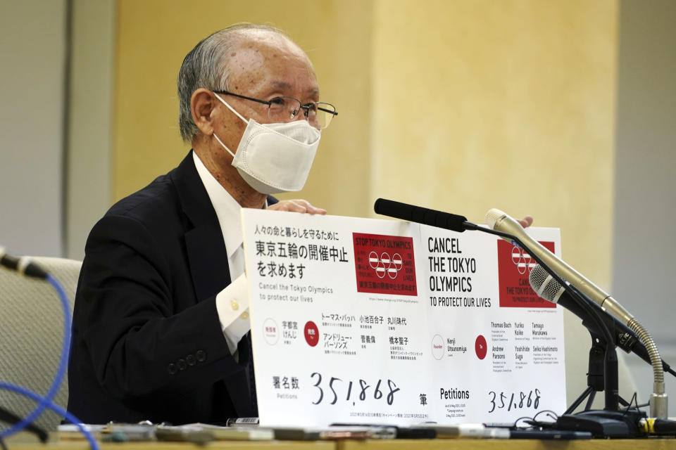 Lawyer Kenji Utsunomiya, a representative of an anti-Olympics group, holds boards showing the current figure of online petition during a press conference after submitting a petition to the Tokyo government calling for the cancellation of the Tokyo 2020 Olympics and Paralympics. An online petition calling for the Tokyo Olympics to be cancelled has been submitted to the Tokyo government with over 350,000 signatures on Friday morning. The rollout of the petition comes with Tokyo, Osaka and several other areas under a state of emergency with coronavirus infections rising - particularly new variants. (AP Photo/Eugene Hoshiko)