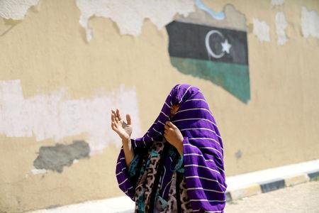 FILE PHOTO: A Libyan displaced woman, who fled her house because of the fighting between the Eastern forces commanded by Khalifa Haftar and the internationally recognised government, reacts at Bader School, which is used as a shelter, in Tripoli, Libya April 14, 2019. REUTERS/Ahmed Jadallah/File Photo