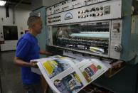 """A worker handles a sample of the newspaper """"Enterate,"""" at a private printing shop in Caracas, Venezuela, Monday, July 26, 2021. Journalists are giving free copies of """"Enterate"""" to bus passengers and people at bus stops, and encouraging them to share the papers with others. (AP Photo/Ariana Cubillos)"""