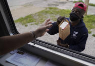 A man receives Narcan and other medical supplies from a mobile window during a harm reduction effort in St. Louis on Friday, May 21, 2021. (AP Photo/Brynn Anderson)