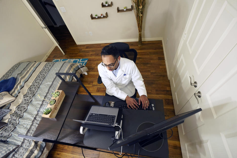 Medical director of Doctor on Demand Dr. Vibin Roy types notes as he listens to a patient during an online primary care visit from his home, Friday, April 23, 2021, in Keller, Texas. Some U.S. employers and insurers want you to make telemedicine your first choice for most doctor visits. Retail giant Amazon and several insurers have started or expanded virtual-first care plans to get people thinking telemedicine routinely, even for annual checkups. (AP Photo/LM Otero)
