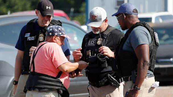 PHOTO: Domingo Candelaria, a registered immigrant, shows federal agents his identification as he prepares to leave the Koch Foods Inc., plant in Morton, Miss., following a raid by U.S. immigration officials, Wednesday, Aug. 7, 2019. (AP Photo/Rogelio V. Solis)