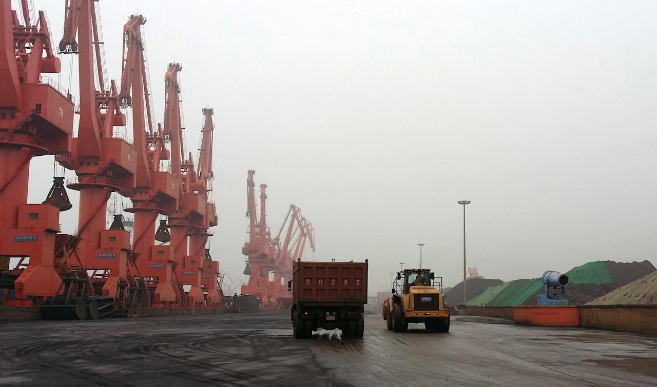 FILE PHOTO: Trucks drive inside an iron ore dump site at the Huanggang Terminal of Qingdao Port, in Qingdao, Shandong Province, China June 7, 2014.  REUTERS/Fayen Wong/File Photo