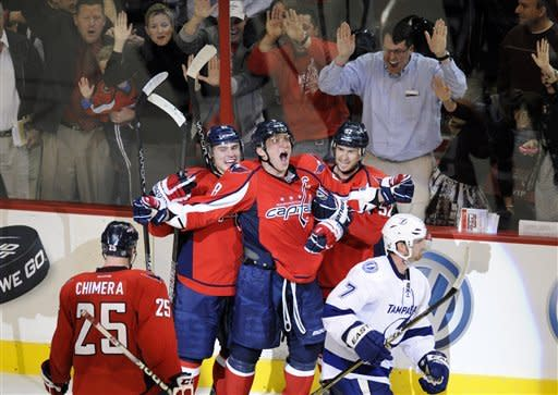 Washington Capitals left wing Alex Ovechkin, center, of Russia, screams and celebrates his game-winning goal with teammates Mike Green, right, Dmitry Orlov, of Russia, second from left, and Jason Chimera (25) as Tampa Bay Lightning defenseman Brett Clark (7) skates away during the overtime period of an NHL hockey game, Thursday, March 8, 2012, in Washington. The Capitals won 3-2 in overtime. (AP Photo/Nick Wass)