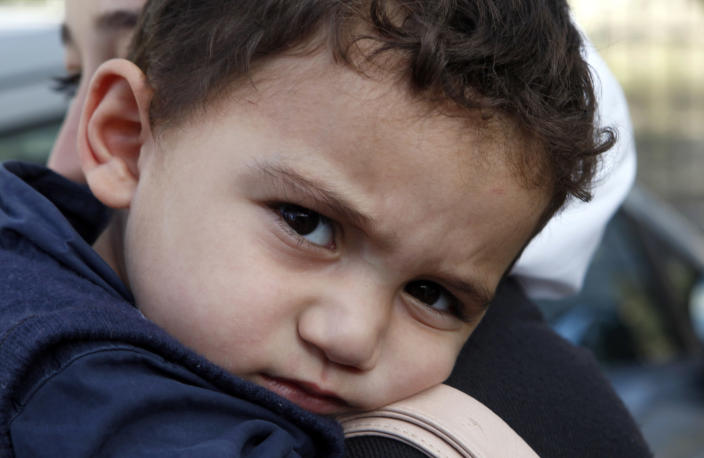 """Bushr Al Tawashi looks at the photographer as he is carried by his mother Arin Al Dakkar, outside of a private Sigma TV station, in Nicosia, Cyprus, Friday, Oct. 26, 2012. Bushr Al Tawashi, a 2-year-old Syrian boy who was believed dead after his family inadvertently left him behind as they fled shelling in Damascus last summer has been reunited with his parents in Cyprus, a lawyer said. """"You can imagine how they felt when they were told their son was alive after bearing all this guilt thinking that he was dead,"""" lawyer Stella Constantinou told The Associated Press. (AP Photo/Petros Karadjias)"""