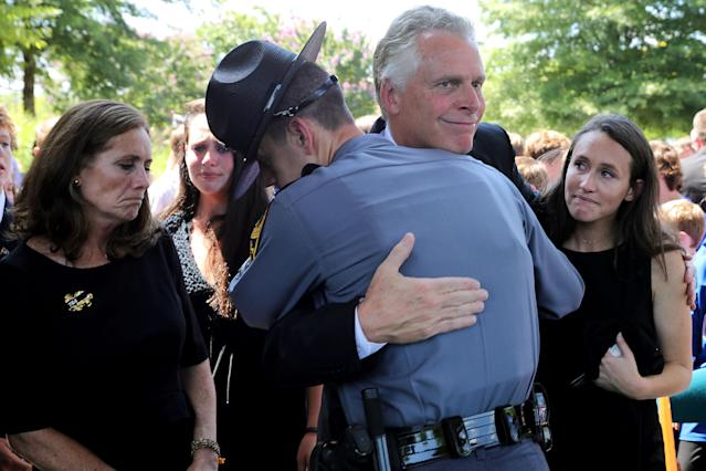 Then-Virginia Gov. Terry McAuliffe is embraced by a state trooper after the funeral for Trooper-Pilot Berke M.M. Bates in Richmond, Aug. 18, 2017. (Photo: Chip Somodevilla/Getty Images)