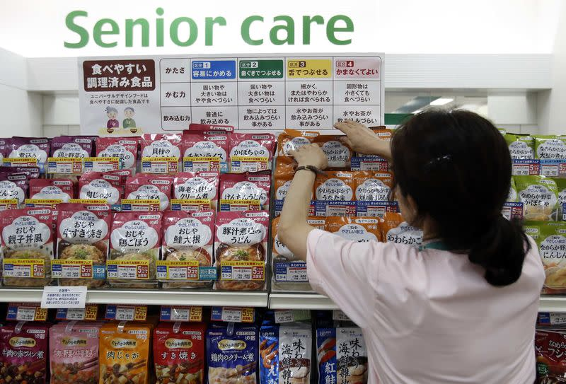 A staff arranges Kewpie Corp's nursing care food packages on a display shelf at an Ito-Yokado shopping centre in Tokyo