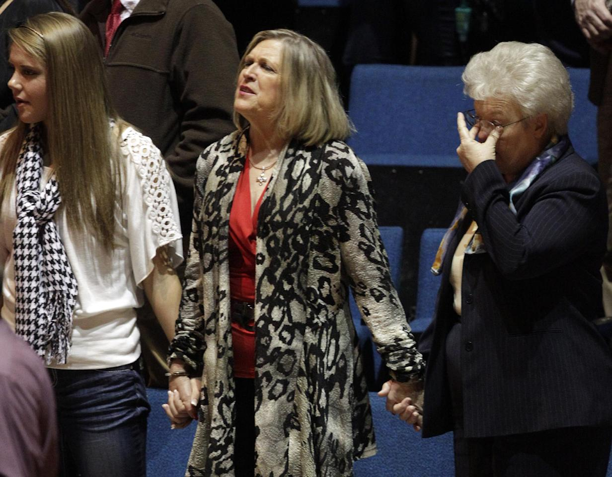 "Friends and family sing and cry as they gather to pay respects for Charles ""Chuck"" Poland at the Ozark Civic Center on Sunday, Feb. 3, 2013, in Ozark, Ala. Authorities say Jim Lee Dykes, 65 — a decorated veteran of the Vietnam War known as Jimmy to neighbors — gunned down Poland a school bus driver and then abducted a 5-year-old boy from the bus, taking him to an underground bunker on his rural property. (AP Photo/Butch Dill)"