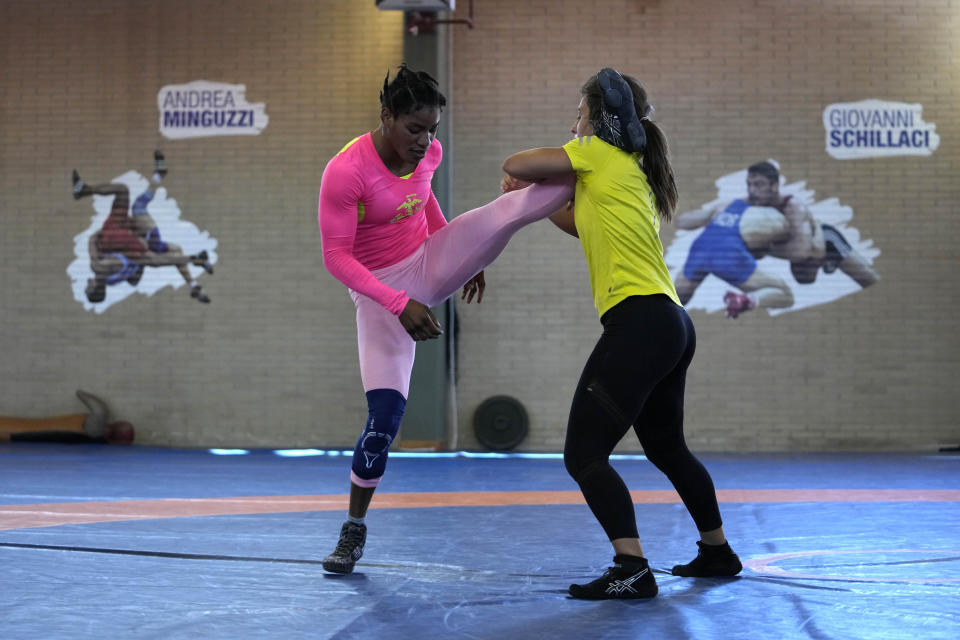 Guinean wrestler Fatoumata Yarie Camara, left competes with Italian athlete Morena De Vita during her morning training session at the Ostia's Olympic training center, near Rome, Monday, July 5, 2021. A West African wrestler's dream of competing in the Olympics has come down to a plane ticket. Fatoumata Yarie Camara is the only Guinean athlete to qualify for these Games. She was ready for Tokyo, but confusion over travel reigned for weeks. The 25-year-old and her family can't afford it. Guinean officials promised a ticket, but at the last minute announced a withdrawal from the Olympics over COVID-19 concerns. Under international pressure, Guinea reversed its decision. (AP Photo/Alessandra Tarantino)