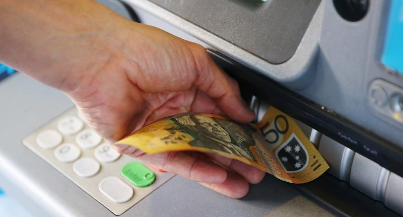 Photo shows a person inserting a $50 note into an ATM.