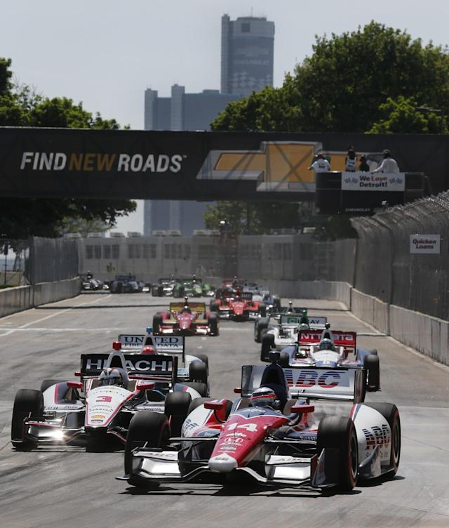 Takuma Sato (14), of Japan, leads the field into turn one on a restart during the second race of the IndyCar Detroit Grand Prix auto racing doubleheader in Detroit Sunday, June 1, 2014. (AP Photo/Paul Sancya)