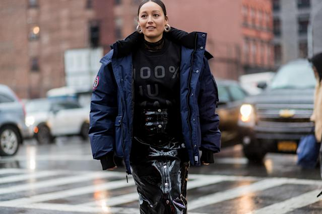 <p>Stylist Rachael Wang is wearing an Everlane T-shirt, navy puffer coat, and black patent-leather skirt. This is a chic and feminine way to mix and match unexpected textures while still looking haute-fashion in the cold. (Photo: Getty Images) </p>