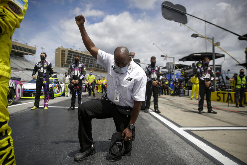 FILE - In this June 7, 2020, file photo, a NASCAR official kneels during the national anthem before a NASCAR Cup Series auto race at Atlanta Motor Speedway in Hampton, Ga. The largest auto racing series in North America for years had specific guidance for its teams to stand, helmetless and hatless, with right hands over the heart during the anthem. That language was removed less than a month ago as NASCAR goes through a reckoning of its own. (AP Photo/Brynn Anderson, File)