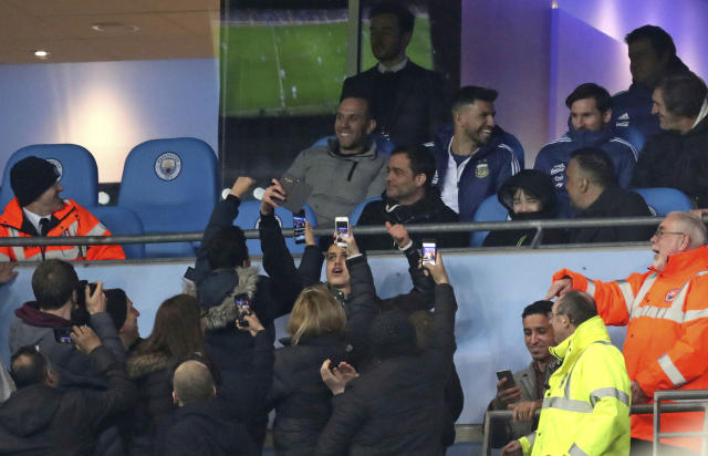 Fans in the stands take photos of Lionel Messi and Sergio Aguero as stewards attempt to stop them during during the international friendly soccer match between Argentina and Italy at the Etihad Stadium in Manchester, England, Friday, March 23, 2018. (Martin Rickett, PA via AP)